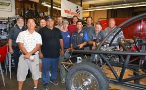 Automotive teachers gathered with frame of electric car.