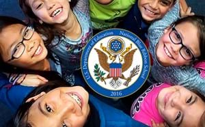 Kids joined in a circle smiling up to the camera with Blue Ribbon School seal in the center.