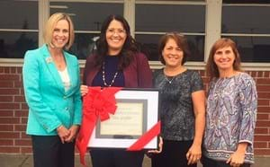 Principal receiving statewide award by GGUSD members.