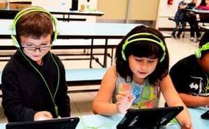 Young students working on tablets.