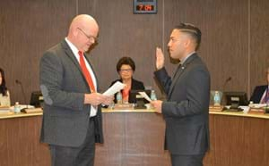 Santiago principal swearing in Walter Muneton as new board member.