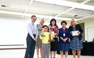 Elementary school spelling bee champion celebrating his win with trophies alongside GGUSD members and administrators.