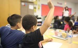 Student raising his hand in class.