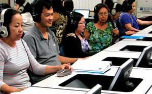 Adults taking a technology class, wearing headphones that allows translation through the course.