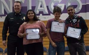 Three Santiago students being recognized by a local community fire fighter.