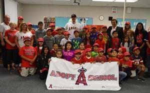 Several students and teachers with Anaheim Angels gear and Adopt a School banner.