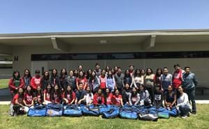 Several high school students with duffel bags full up supplies ready to donate to foster kids.