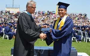 High School student receiving diploma at graduation.