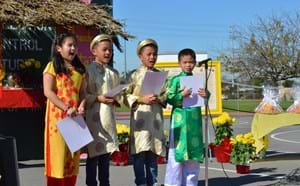 Four students performing in traditional Vietnamese attire.