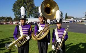 Three Santiago band members in full uniform and their instruments.