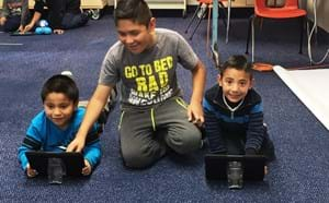 Two young students on a tablet while an older student helps.