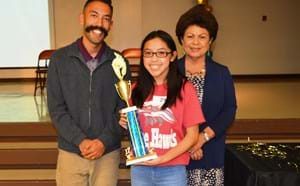 Top Speller displaying trophy with GGUSD board members.