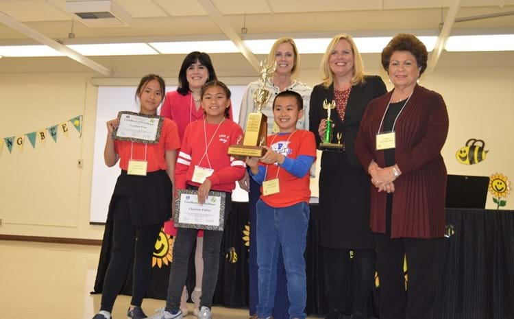 Elementary school spelling bee champions displaying awards and trophies with GGUSD administrators.
