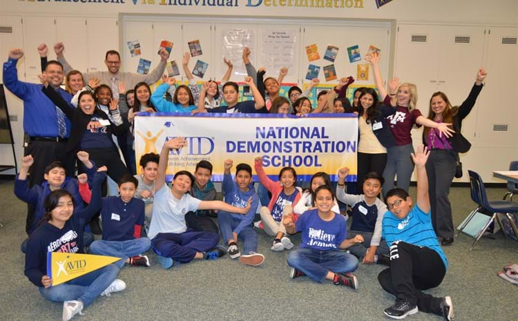 AVID students and teachers celebrate highest recognition with hands in the air.