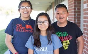 Three smiling elementary students.