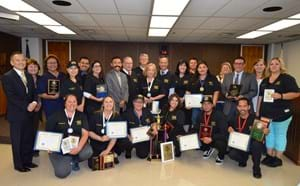 Several bus drivers and GGUSD administrators displaying awards and trophies won.
