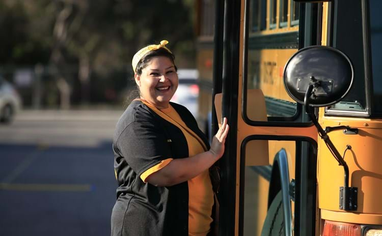 Bus driver along side her bus.