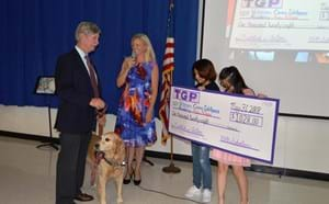 Murdy students and teacher present donation to veteran accompanied by his dog.