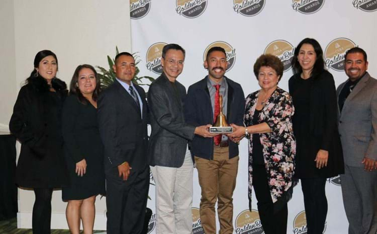 Monroe staff and board of education members accepting Golden Bell Award