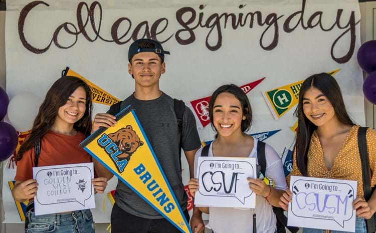 Santiago High School students holding up their colleges of choice during the 2017-18 school year.